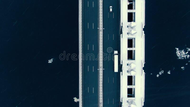 Vista aérea de surpresa verticalmente abaixo da estrada através da baía na queda de neve Tiro do zangão fotografia de stock royalty free