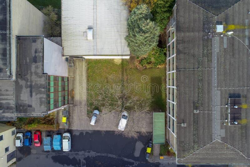 Vista aérea de vista surreal da perspectiva vertical de carros de estacionamento entre construções industriais velhas fotos de stock royalty free