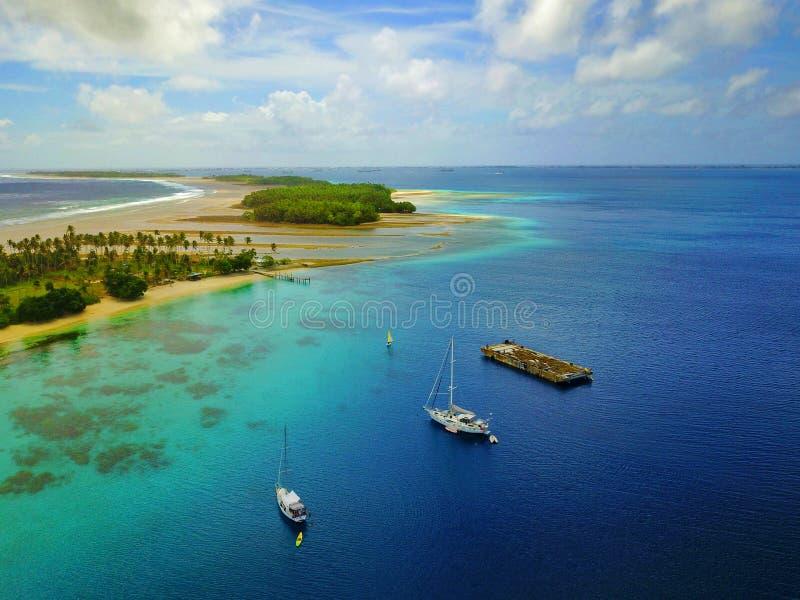Vista aérea de um atol bonito com vila e os iate amarrados imagens de stock
