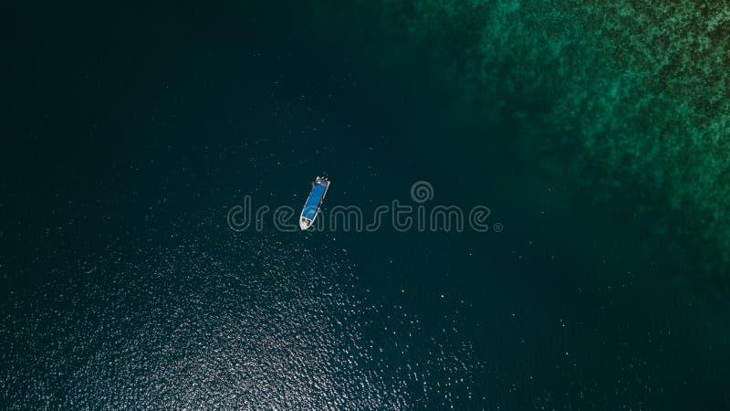 Vista aérea de um barco ao lado de um recife no meio do mar fotografia de stock royalty free