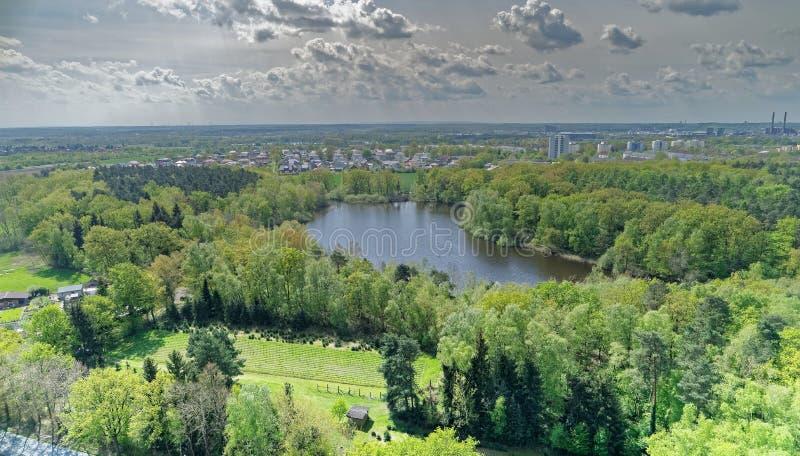 Vista aérea de um lago pequeno no meio da floresta atrás das facilidades industriais da cidade fotografia de stock royalty free