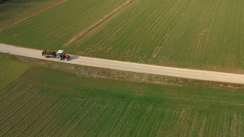 Vista aérea de um trator e de um reboque vermelhos que levam uma carga do estrume na estrada imagem de stock