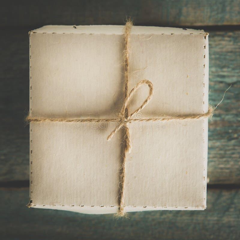 Vista aérea de uma única caixa de presente de época natalícia amarrada com guita Formato quadrado em uma tabela de madeira rústic imagem de stock