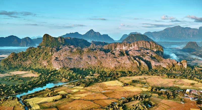Vista aérea de uma cidade pequena no vale e no rio da montanha rochosa imagens de stock