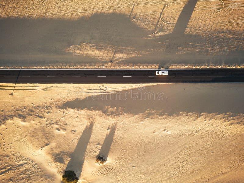 Vista aérea de uma estrada de asfalto reto preto com areia e deserto de ambos os lados - carro que viaja no meio - conceito de foto de stock