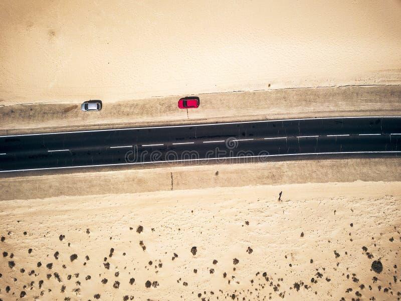 Vista aérea de uma estrada de asfalto reto preto com areia e deserto de ambos os lados - dois carros estacionados ao lado - conce fotografia de stock