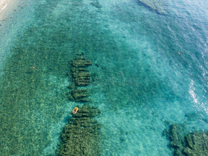 Vista aérea de un bote en el agua que flota en un mar transparente Bañistas en el mar Zambrone, Calabria, Italia imagenes de archivo