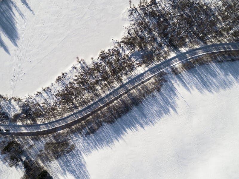 Vista aérea de un camino del invierno entre el lago congelado dos Campo del paisaje del invierno Fotografía del bosque nevoso y c imagen de archivo libre de regalías
