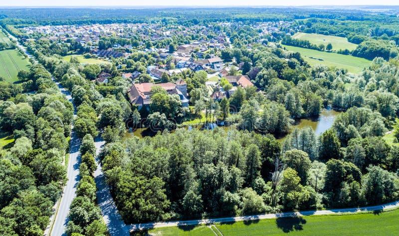 Vista aérea de un pueblo alemán con un pequeño bosque, una charca y un castillo moated en el primero plano fotos de archivo