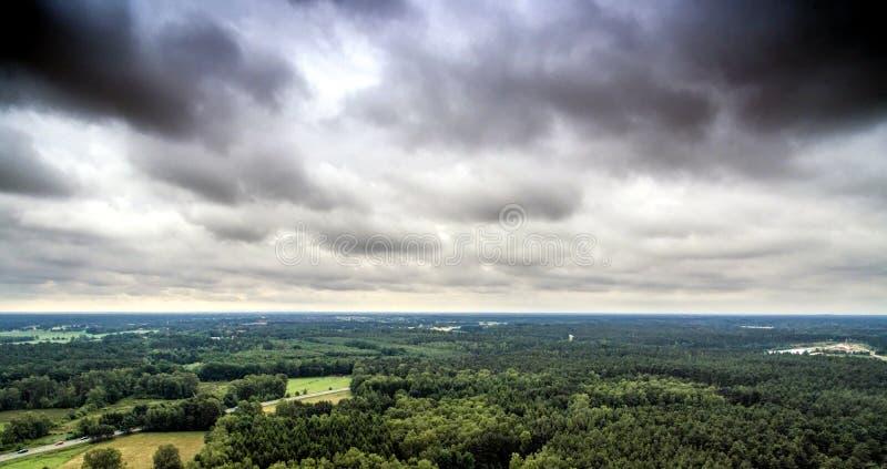Vista aérea de una área arbolada densa en Alemania, que es cruzada por un camino en el borde de una ciudad, con el cielo dramátic fotos de archivo libres de regalías