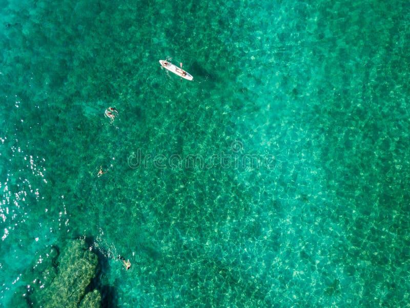Vista aérea de una canoa en el agua que flota en un mar transparente Bañistas en el mar Zambrone, Calabria, Italia imagen de archivo libre de regalías