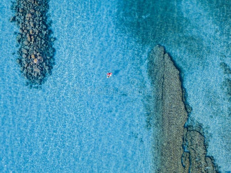 Vista aérea de una canoa en el agua que flota en un mar transparente Bañistas en el mar Zambrone, Calabria, Italia fotos de archivo libres de regalías