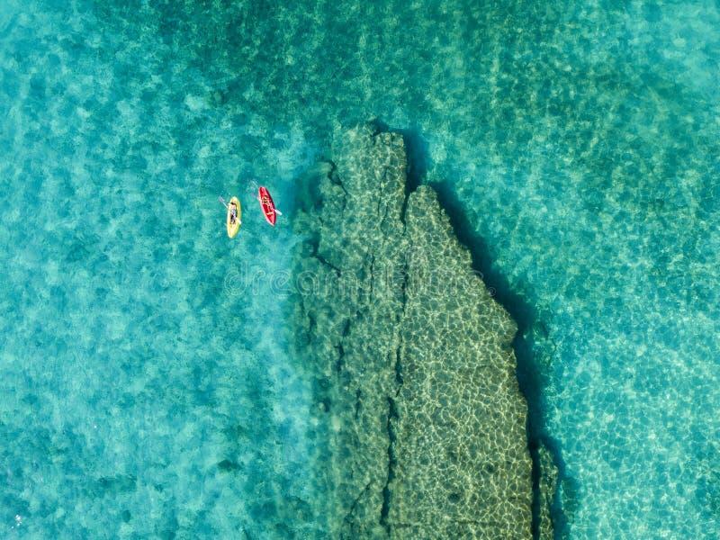 Vista aérea de una canoa en el agua que flota en un mar transparente Bañistas en el mar Zambrone, Calabria, Italia fotos de archivo