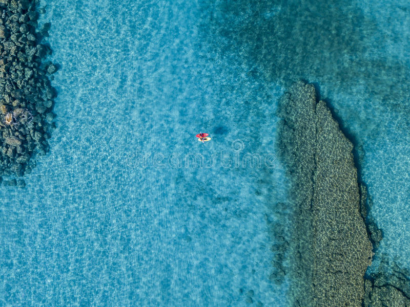 Vista aérea de una canoa en el agua que flota en un mar transparente Bañistas en el mar Zambrone, Calabria, Italia imagenes de archivo