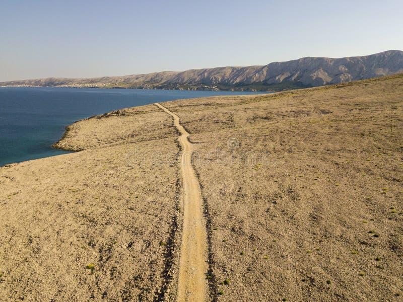 Vista aérea de una carretera con curvas que corre a lo largo de las costas croatas, camino de tierra, isla del Pag cerca de la pl imagen de archivo libre de regalías