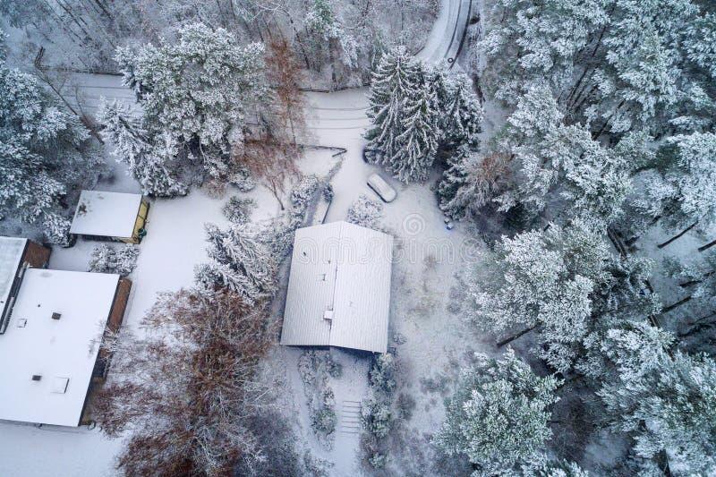 Vista aérea de una casa unifamiliar en el bosque durante los wi imagen de archivo