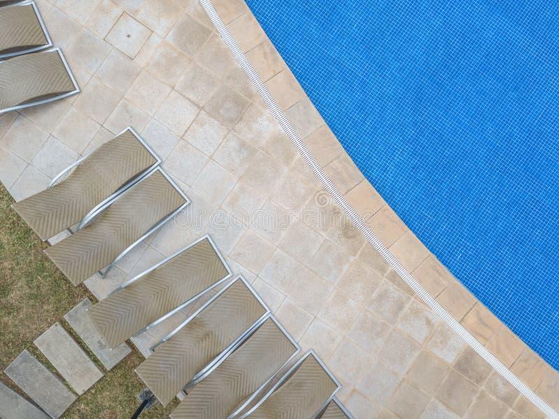 Vista aérea del abejón, de la piscina del agua transparente y del fondo azul con los ociosos del sol en el pavimento de piedra imágenes de archivo libres de regalías