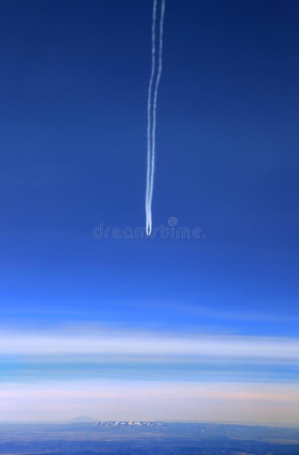 Vista aérea del avión con la estela de vapor que vuela sobre las montañas distantes foto de archivo