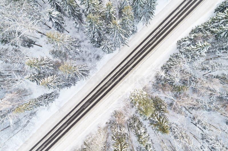 Vista aérea del camino en bosque del invierno imagenes de archivo