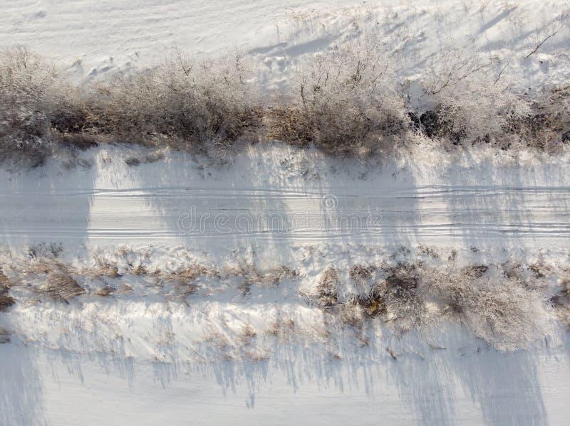 Vista aérea del camino nevoso en el campo, visión superior Invierno, desastre del tiempo Área de tráfico difícil foto de archivo libre de regalías