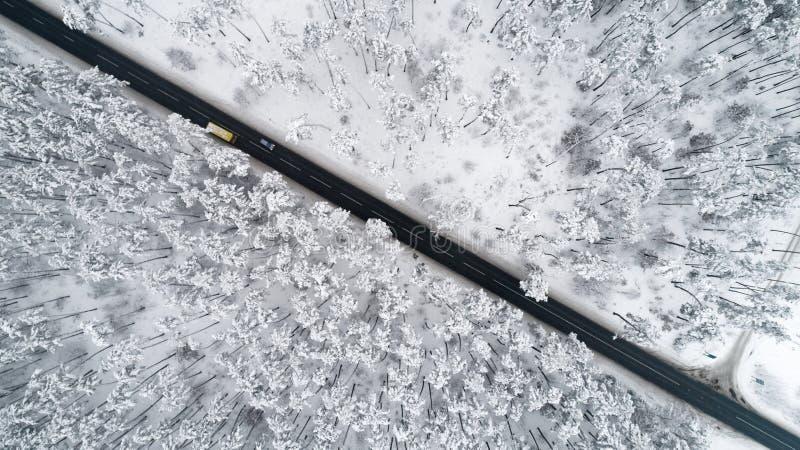 Vista aérea del camino romántico que pasa con la opinión superior del bosque nevado del invierno fotos de archivo