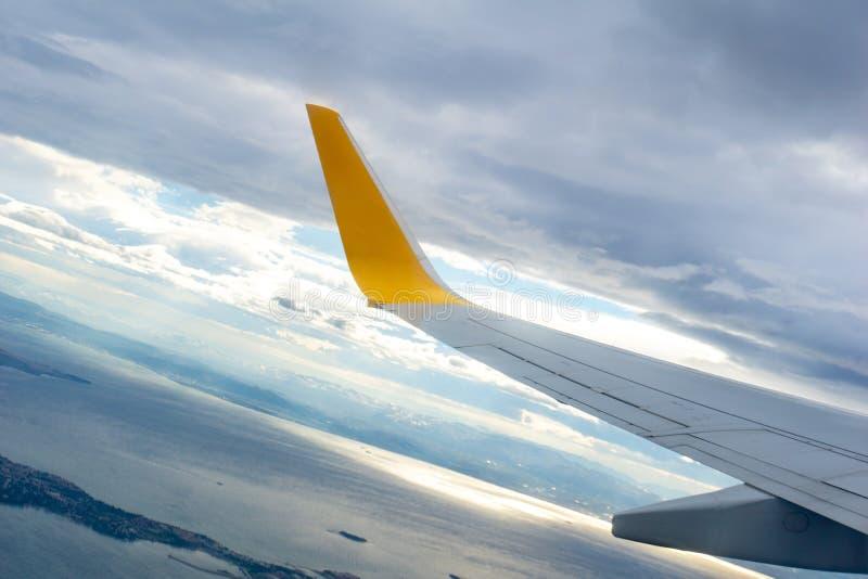 Vista aérea del cielo azul y a través de la ventana vista nube de un avión, ala del aeroplano de la ventana fotos de archivo
