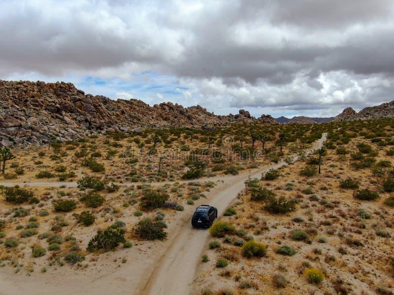 Vista aérea del coche 4x4 que elimina el camino en el desierto árido fotografía de archivo