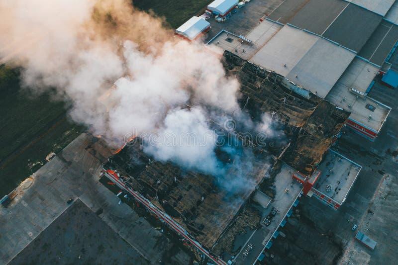 Vista aérea del edificio industrial ardiente demolido por el fuego, del humo enorme del tejado quebrado, de las paredes y de las  imágenes de archivo libres de regalías