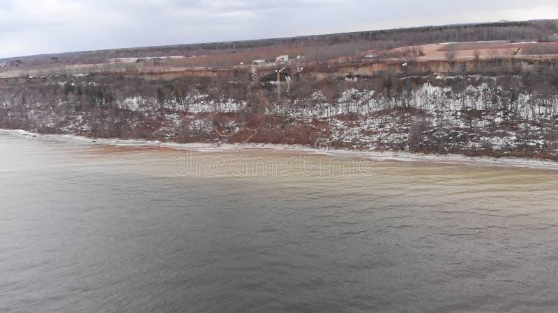 Vista aérea del río ancho y de la orilla nevosa con los árboles que crecen en la colina, naturaleza en invierno existencias Paisa imagen de archivo