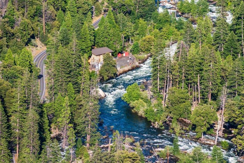 Vista aérea del río de Merced que atraviesa un bosque conífero; estación de la energía eléctrica y camino pavimentado visibles a  foto de archivo libre de regalías