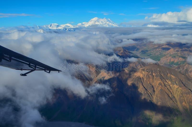 Vista aérea del soporte Denali - pico del mt Mckinley de un avión con las montañas coloridas alrededor y el cielo azul arriba den fotografía de archivo libre de regalías