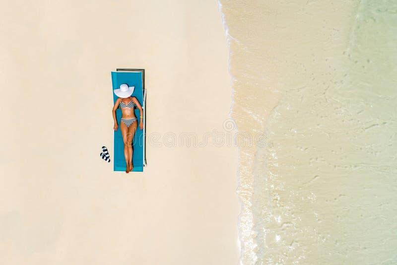 Vista aérea do banho de sol magro da mulher que encontra-se em uma cadeira de praia em Maldivas Seascape do ver?o com menina, ond fotos de stock