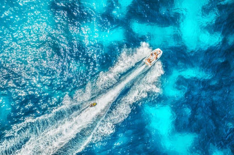 Vista aérea do barco a motor de flutuação no mar azul transparente foto de stock royalty free
