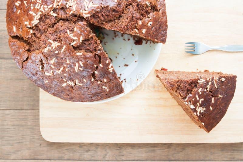 Vista aérea do bolo de chocolate da banana com uma parte do corte na madeira fotografia de stock