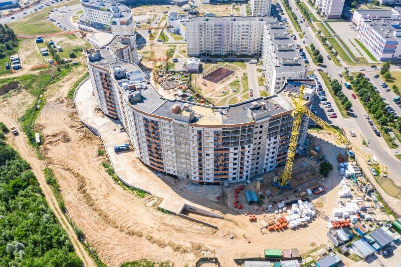 Vista aérea do canteiro de obras da cidade com o guindaste de torre industrial amarelo alto imagem de stock