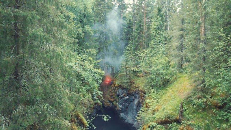 Vista aérea do homem de pé na borda de uma cordilheira profunda com sinal vermelho flare em sua mão na floresta perto do velho al fotografia de stock