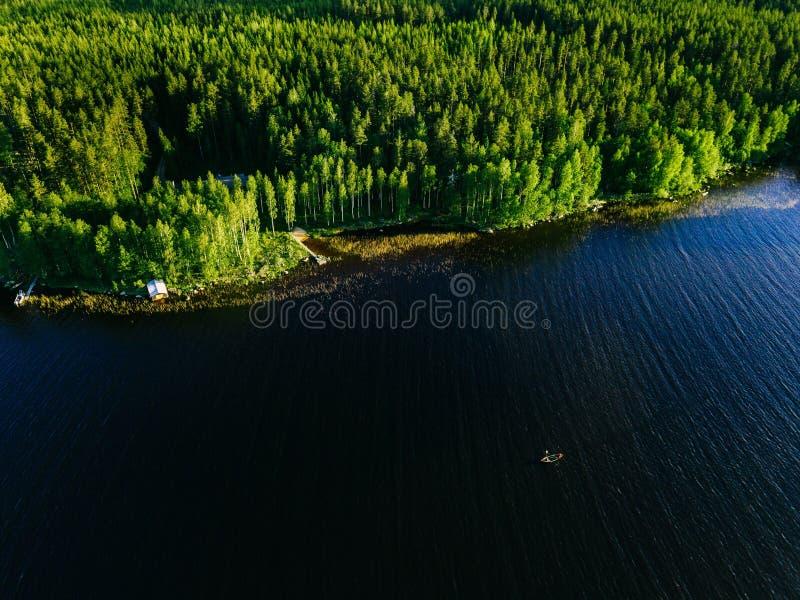 Vista aérea do lago azul com um barco de pesca e umas madeiras verdes em um dia de verão ensolarado em Finlandia imagens de stock royalty free