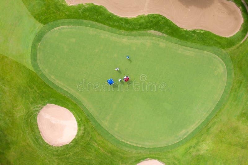 Vista aérea dos jogadores num campo de golfe verde Golfer tocando verde num dia de verão fotografia de stock royalty free