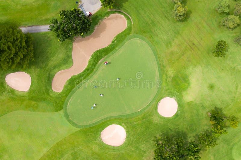 Vista aérea dos jogadores num campo de golfe verde Golfer tocando verde num dia de verão Tempo de relaxamento do estilo de vida d imagens de stock royalty free