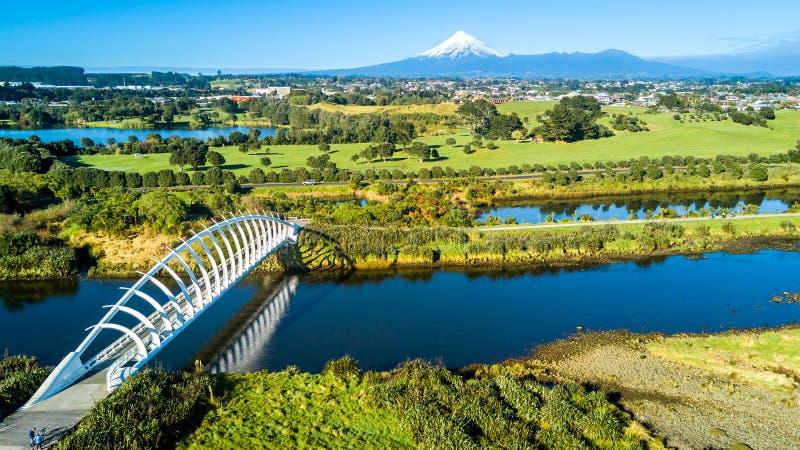 Vista aérea em uma ponte bonita através de um córrego pequeno com montagem Taranaki no fundo Em algum lugar em Nova Zelândia fotografia de stock