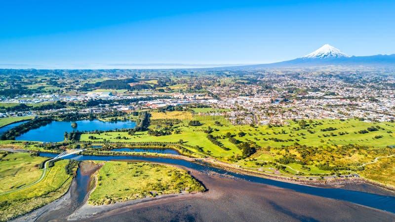 Vista aérea em uma ponte bonita através de um córrego pequeno com montagem Taranaki no fundo Em algum lugar em Nova Zelândia fotos de stock