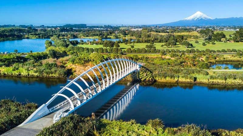 Vista aérea em uma ponte bonita através de um córrego pequeno com montagem Taranaki no fundo Em algum lugar em Nova Zelândia foto de stock