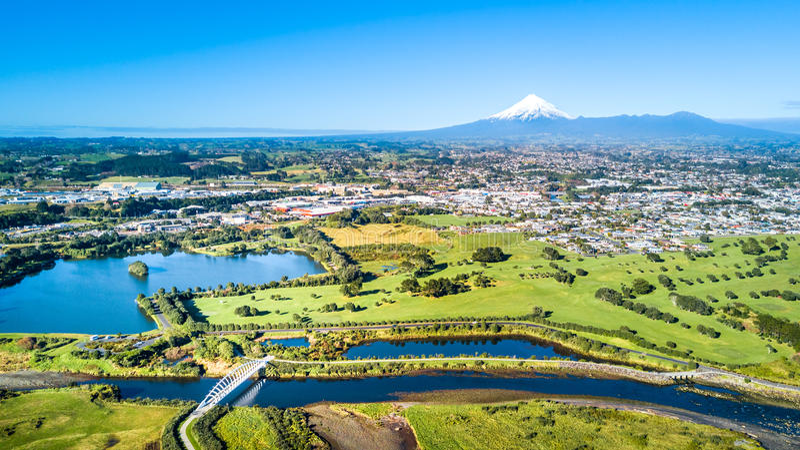 Vista aérea em uma ponte bonita através de um córrego pequeno com montagem Taranaki no fundo Em algum lugar em Nova Zelândia imagens de stock