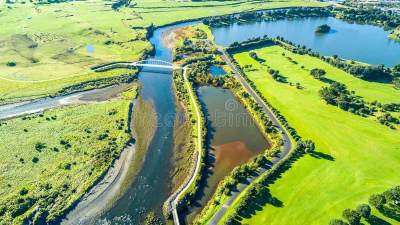 Vista aérea em uma ponte bonita através de um córrego pequeno com subúrbio residencial no fundo Em algum lugar em Nova Zelândia foto de stock royalty free