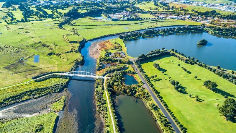 Vista aérea em uma ponte bonita através de um córrego pequeno com subúrbio residencial no fundo Em algum lugar em Nova Zelândia fotos de stock royalty free