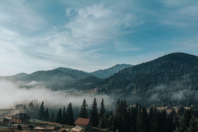 Vista aérea incrível sobre as montanhas Cárpticas ou Cárpatos com linda paisagem de outono, nascer do sol, céu azul com branco fotografia de stock royalty free