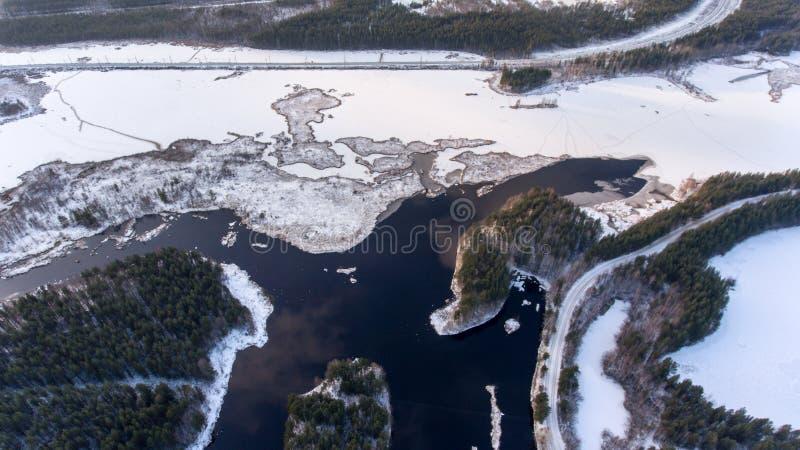 Vista aérea na estrada de trilho do norte que passa ao longo do lago parcialmente congelado na floresta no dia de inverno frio, C imagens de stock