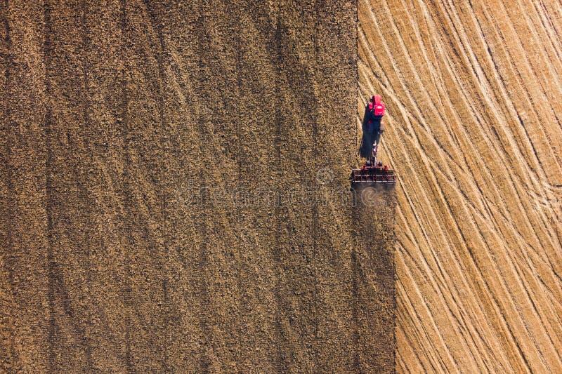Vista aérea na liga que trabalha no grande campo de trigo feno imagem de stock royalty free