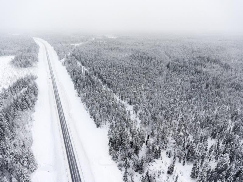 A vista aérea na linha de estrada escorregadiço do inverno em Taiga nublado é sobre ao norte de Rússia fotos de stock royalty free