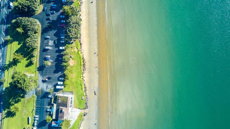Vista aérea na praia ensolarada com estacionamento do carro Auckland, Nova Zelândia imagens de stock royalty free